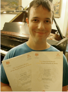 Josh Tyree with Royal School of Music Certificates for the Theory and Piano Performance tests.